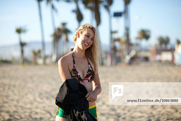 Young female surfer holding wetsuit on Venice Beach  California  USA