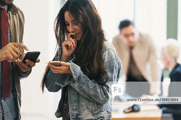 Kollegen mit Smartphone im Büro