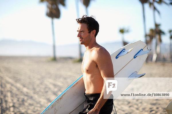 Männlicher Surfer mit Surfbrett am Strand von Venice Beach  Kalifornien  USA