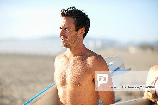 Männlicher Surfer mit nacktem Oberkörper und Surfbrett am Strand von Venice Beach  Kalifornien  USA