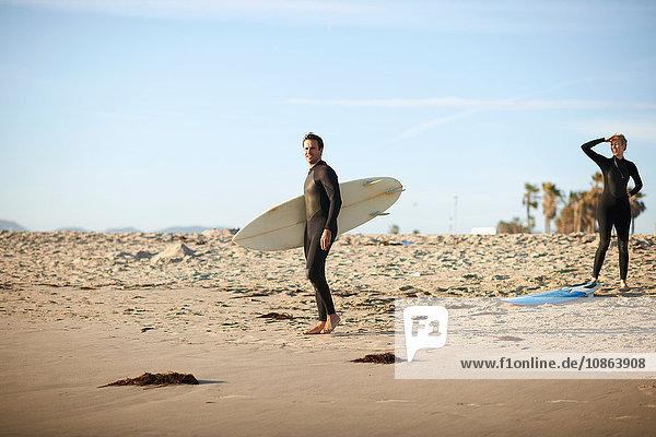 Surferpaar mit Surfbrettern am Strand von Venice Beach  Kalifornien  USA