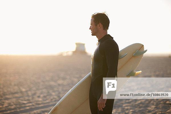 Männlicher Surfer mit Surfbrett mit Blick auf Venice Beach  Kalifornien  USA