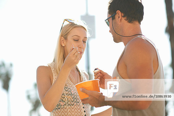 Couple sharing frozen yoghurt at Venice Beach  California  USA