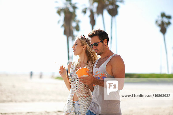 Couple strolling and sharing frozen yoghurt at Venice Beach  California  USA