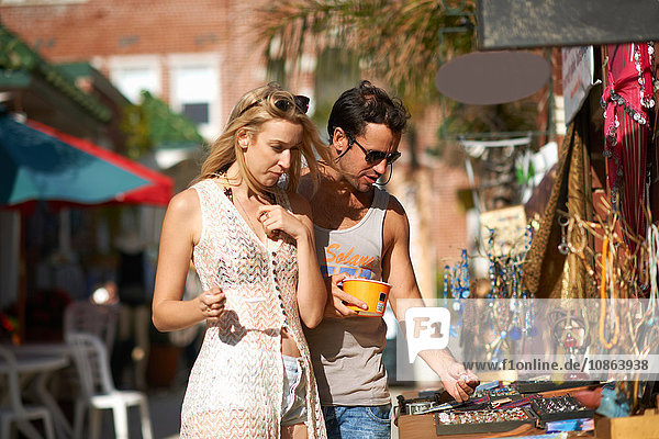 Couple eating frozen yoghurt and browsing jewellery stall at Venice Beach  California  USA