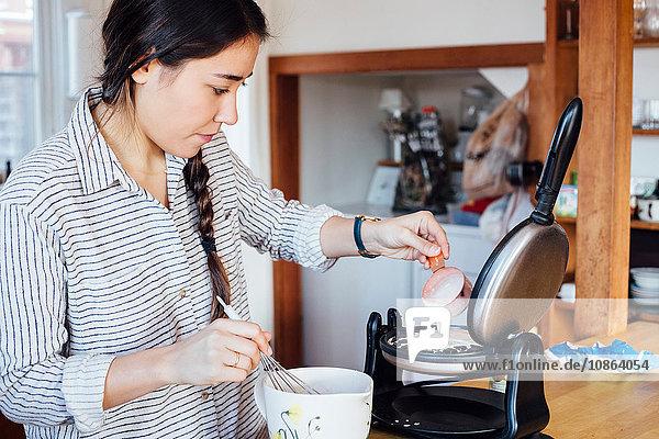 Frau in der Küche fügt Teig zum Waffeleisen hinzu