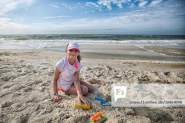 Girl sitting on beach playing in sand  looking at camera smiling