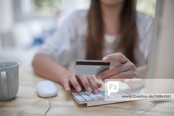 Frau  die beim Online-Shopping mit Kreditkarte bezahlt