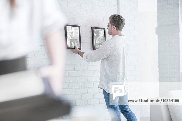 Mann hängt Bilder im Raum auf