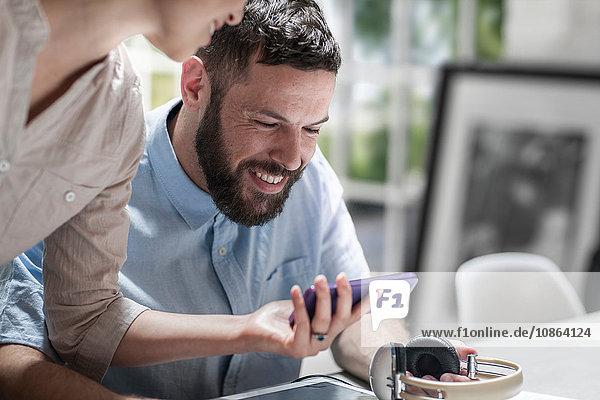 Paar lächelt über Nachricht auf Smartphone