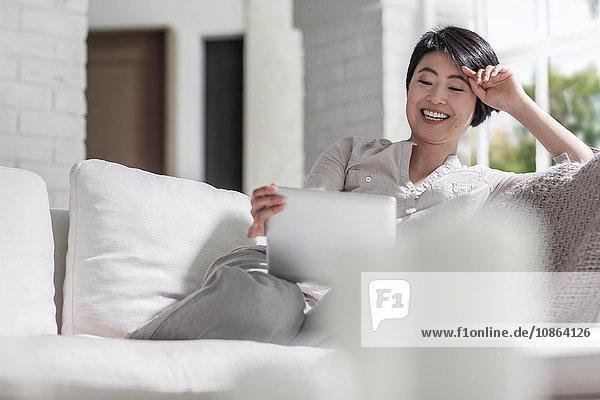 Frau benutzt digitales Tablett auf dem Sofa