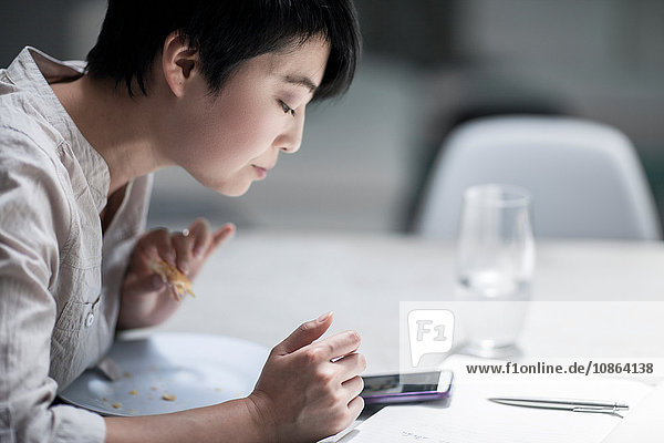 Woman using smartphone while eating