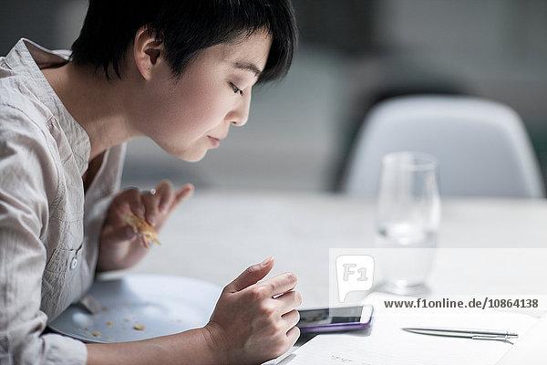 Frau benutzt Smartphone beim Essen
