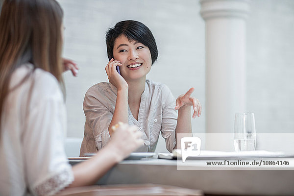 Frauen im Chat  eine davon mit Smartphone