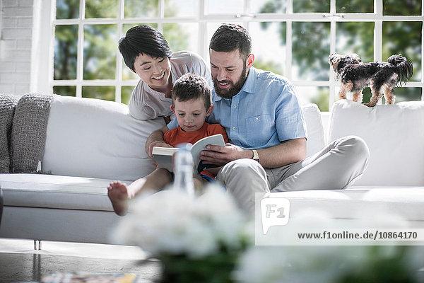 Ehepaar unterrichtet Sohn beim Lesen eines Buches auf dem Sofa