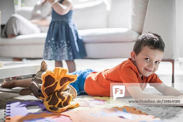 Junge auf Teppich liegend  Personen im Hintergrund