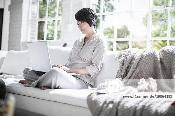 Frau benutzt Laptop auf Sofa neben Haushund