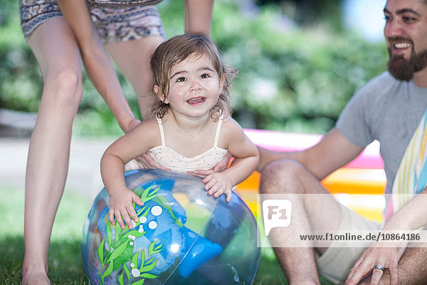 Eltern mit Tochter lehnen sich im Garten an Ball