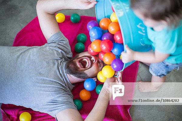 Vater auf dem Boden liegend  Kleinkind schüttet Eimer mit Bällen über sich