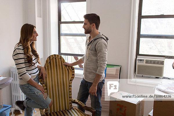 Umzug: Junges Paar lehnt sich auf Stuhl und diskutiert