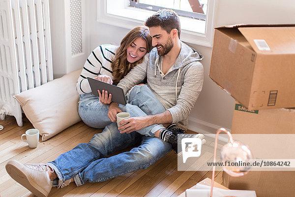 Umzug: Junges Paar sitzt in einem Zimmer voller Kisten und schaut auf ein digitales Tablett