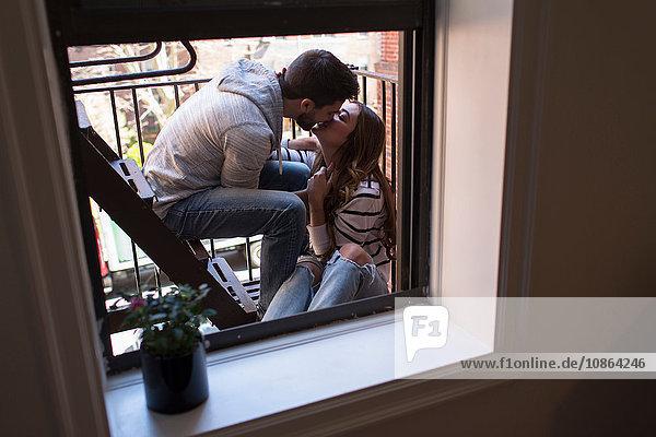 Junges Paar sitzt auf der Feuertreppe und küsst sich