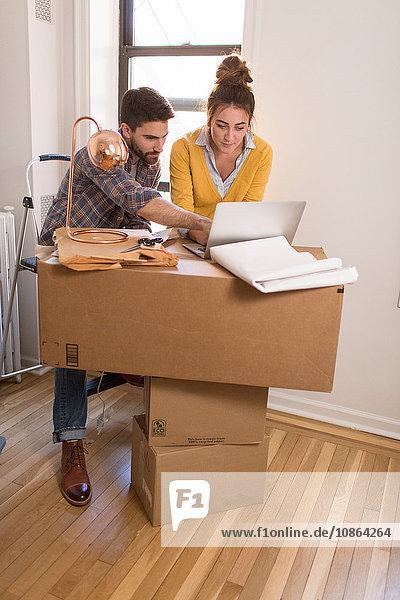 Umzug: Junges Paar lehnt auf Pappkarton und benutzt Laptop