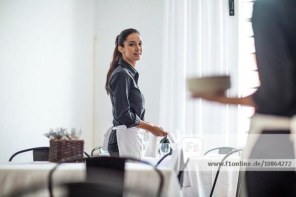 Kellnerinnen decken den Tisch im Restaurant