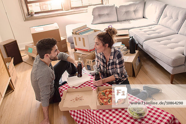 Moving house: Young couple eat pizza in new home  surrounded by boxes