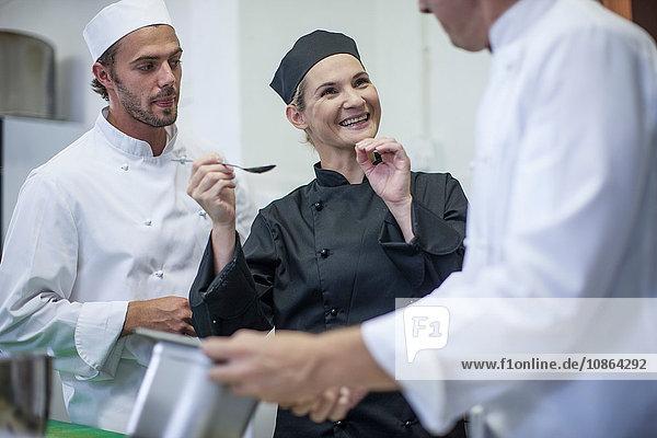 Köche plaudern und probieren Essen in der Küche