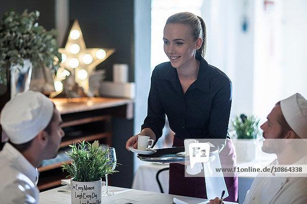 Kellnerin  die den Köchen in der Pause Kaffee serviert