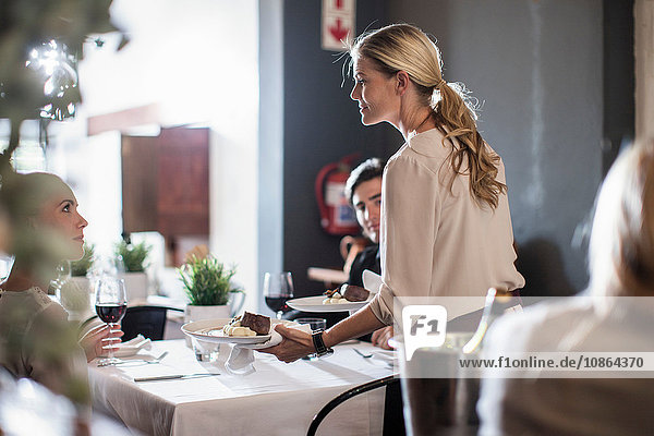 Waitress serving customers in restaurant