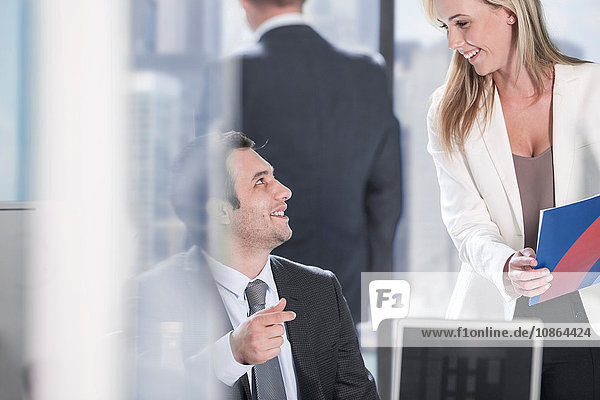 Businessman and businesswoman chatting in office
