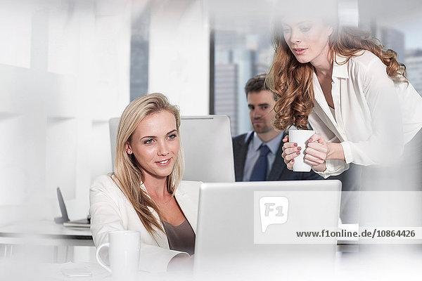 Geschäftsfrau benutzt Laptop im Büro  Kollegin benutzt Computer im Hintergrund