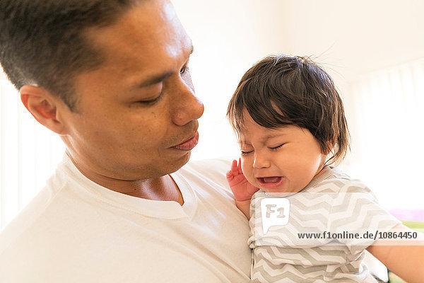 Vater tröstet weinendes Baby