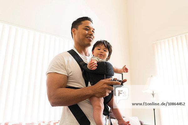 Vater mit Baby im Tragesitz  spielt Videospiel