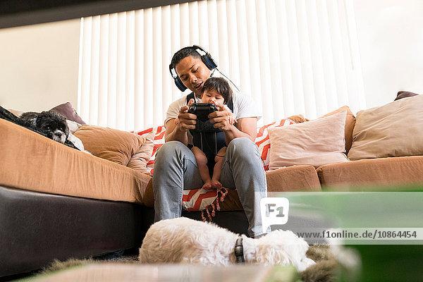 Vater mit Baby im Tragesitz,  spielt Videospiel