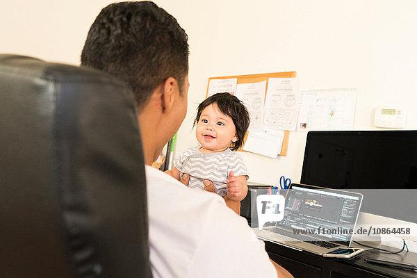 Vater spielt mit Baby am Arbeitstisch