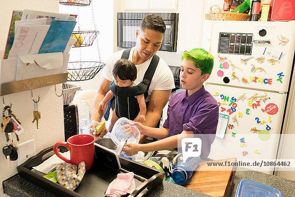 Sohn hilft Vater mit Baby im Gepäck beim Geschirrspülen