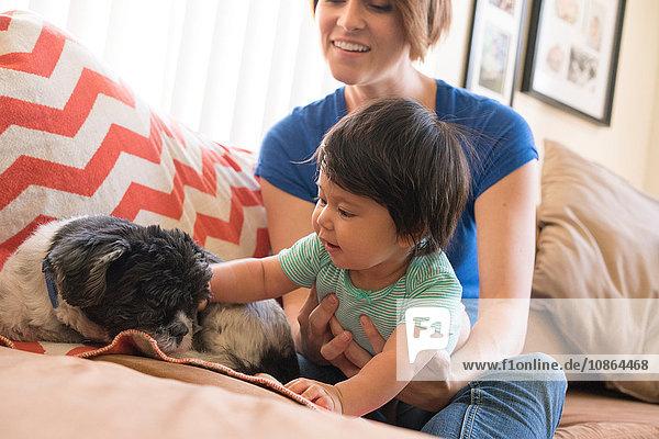 Mutter beobachtet Baby beim Spielen mit Hund auf dem Sofa