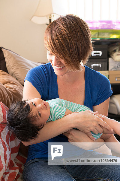 Mutter wiegt Baby auf dem Sofa