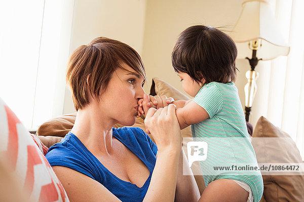 Mutter sitzt auf dem Sofa und küsst Babys Hände