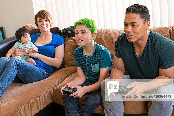Mutter mit Baby beobachtet Vater und Sohn beim Spielen eines Videospiels auf dem Sofa