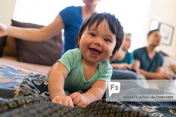 Baby lächelt breit auf dem Sofa  Familie im Hintergrund