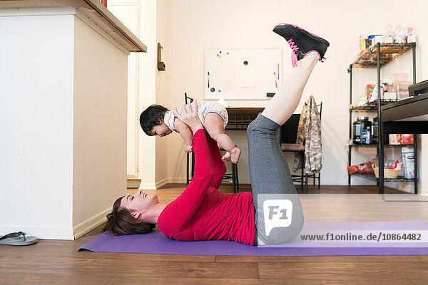 Mutter macht Beinheben mit Baby im Arm