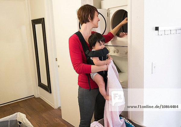 Mutter mit Baby im Tragesitz  Wäsche waschen