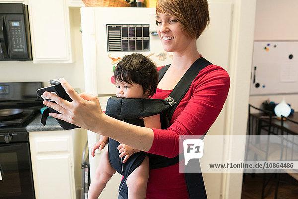 Mutter mit Baby im Gepäckträger  mit Mobiltelefon