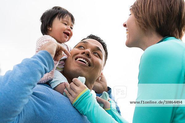 Paar spielt Huckepack-Fahrt mit Baby im Park