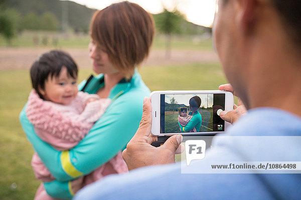 Vater fotografiert Mutter und Baby im Park