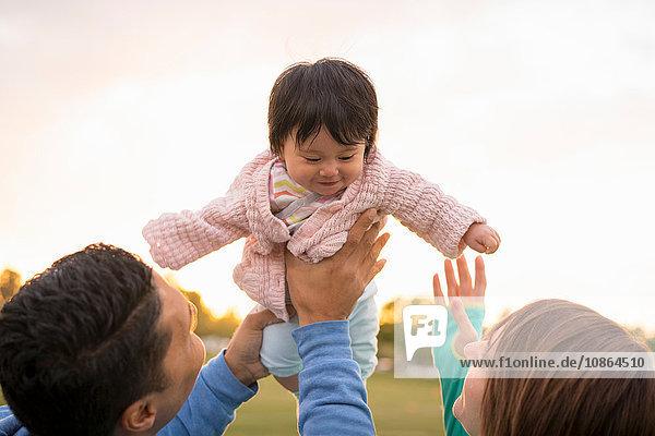 Paar spielt mit Baby im Park